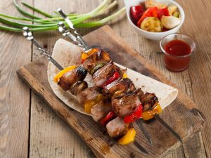 Grilled meat and vegetable kebabs with sauce, selective focus